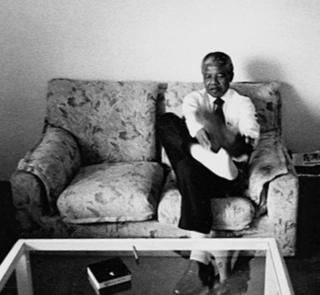 "A photo by Sunmi Smart-Cole entitled: ""Nelson Mandela at ease"" - Kampala, Uganda, 1992, showing the antiapartheid leader taking off his socks"