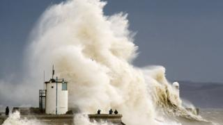 Spectators watch as waves break over the harbour wall at Porthcawl