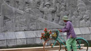 Một người đi qua tượng đài Điện Biên Phủ