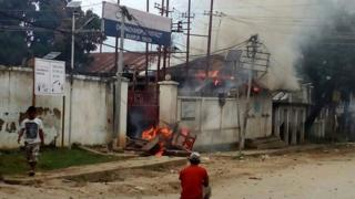 Indian pedestrians walk past a burning police station following violence in the Churachandpur district of the state of Manipur on September 1, 2015.
