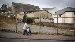 A woman passes a derelict site in Ebbw Vale in Blaenau Gwent, Wales