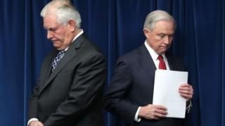 Rex Tilllerson and Jeff Sessions pause before a press briefing announcing the new travel ban.