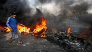 A demonstrator wearing a mask and walking above burning tyres in Basra, southern Iraq