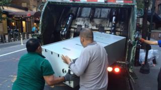 Dos hombres depositan un archivador en un camión de basura en Nueva York.