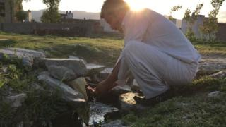 A man washing hands at the well which was located inside the Bin Laden compound once - the compound has now been razed