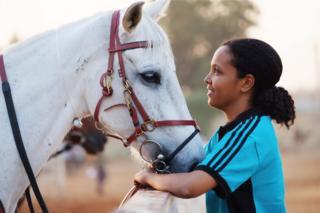 امرأة تقف قرب حصان وتنظر إليه بود