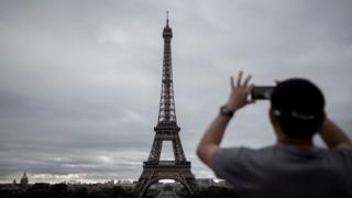 Un hombre toma una foto a la Torre Eiffel