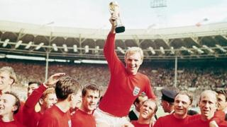Bobby Moore, wearing red, holding the World Cup in 1966
