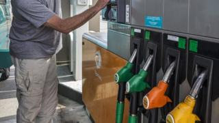 Man selecting fuel pump at Total gas station for refueling his car
