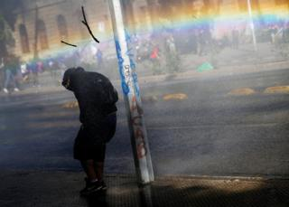 A demonstrator takes cover from tear gas and a water cannon during an anti-government protest in Santiago, Chile.