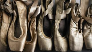 sports Row of old ballet shoes - stock photo