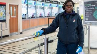Woman cleans hand rail in station ticket office