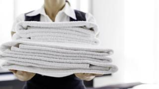Stock image of a maid holding towels