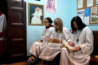 Китаянки-католички в Шанхае ожидают начала службы под изображениями папы Иоанна Павла II и Девы Марии