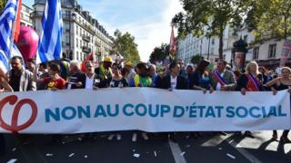 """Protesters hold a banner reading """"no to the social coup d'etat"""" during a demonstration against the French governments labour reforms in Paris, 23 September 2017"""