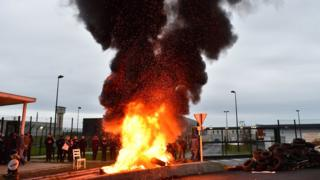 Waste burns as prison guards block the entrance to the penitentiary centre of Alencon, in Conde-sur-Sarthe, northwestern France, on early March 6, 2019