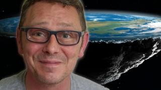 British flat Earther Dave against the backdrop of a flat Earth model.