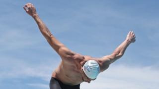"""Antes de girar os braços na água, Michael Phelps o faz no seco para pedir uma """"mãozinha"""" da sorte"""