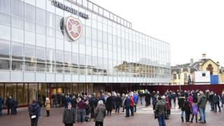 Fans wait outside after a fire alarm causes the evacuation of the main stand at Tynecastle