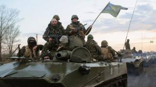 Ukrainian soldiers sit on top of a tank