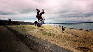 Boy jumping in Crammond, Edinburgh.