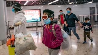 A girl wearing ski goggles and protective mask exits the arrival hall at Hong Kong High Speed Rail Station