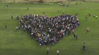 protestors make heart shape
