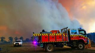 A fire truck and another vehicle parked in front of a massive cloud of smoke from the Long Gully Road fire in October