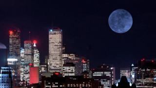 Lua cheia à noite com prédios à frente