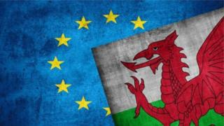 An EU flag and Welsh flag