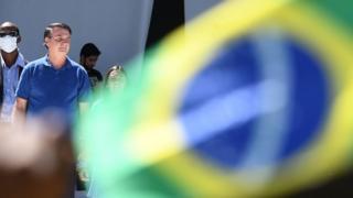 Bolsonaro aparece atrás de bandeira do Brasil e ao lado de segurança com máscara