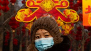 A woman wearing a mask walks under Lunar New Year decorations in Ditan Park on January 26, 2020 in Beijing, China.