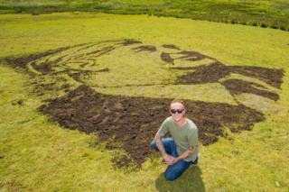 Artist Nathan Wyburn with his portrait of NHS founder Aneurin Bevan which has been unveiled on a Welsh mountainside to celebrate 70 years of the service