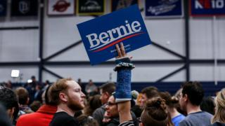Bernie sanders supporter with a cast holding Bernie sign