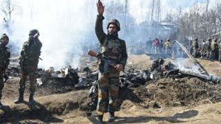 Tentara India di samping puing yang diduga pesawat Angkatan Udara India di Budgam, Kashmir India.
