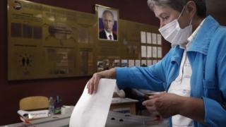 A woman voting in Russia's constitutional referendum under a poster of Vladimir Putin, June 2020