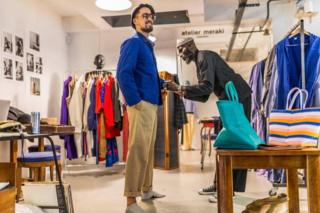Amah styling a client in a vintage blue worker jacket