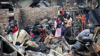 Slum dwellers are seen gather near their shelters after fire burnt them out in Dhaka, Bangladesh, on 17 August 2019