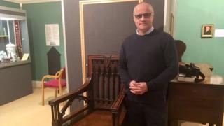 Bard Tudur Dylan Jones standing next to 1819 Eisteddfod chair in Camarthen