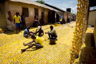 People sewing the yellow tapestry designed by artist Serge Attukwei Clottey on a road in La - Accra, Ghana
