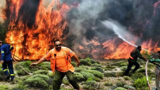 Homens trabalham para apagar o enormes labaredas de fogo na Grécia
