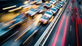 Rastros de farois deixados por carros em pistas de sentido contrário em uma estrada