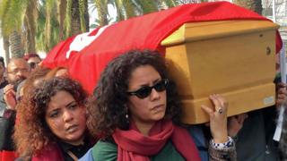 Ines Tlili Zaalouni (front) and Myriam Bribri (back) carry the flag-draped coffin of Lina Ben Mhenni in Tunis, Tunisia - Tuesday 28 January 2020