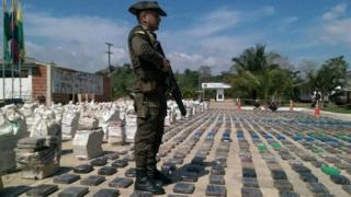並べられた押収物を警備する警官(15日、コロンビア・ツルボ)