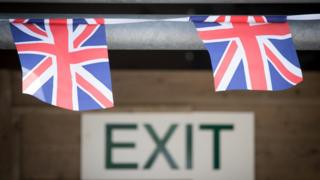 Union jack bunting hangs above an exit sign