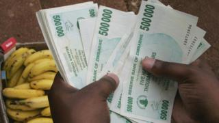 Un Zimbabwéen compte de l'argent pour acheter des bananes à Harare en 2008
