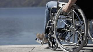 File photo of a man in a wheelchair sitting by water.