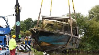 Sunken boat being lifted up from the river