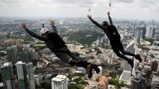 Dos hombres saltan en paracaídas.