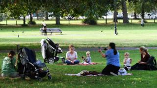 Mothers social distance with their young children at a park in London